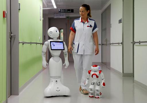 Robotlarla birlikte hastalara daha iyi deneyim verebilmek için iş birliği yapan bir sağlık çalışanı